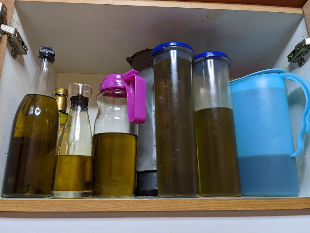 Photo of an open cupboard with 7 containers, each full of dark green olive oil